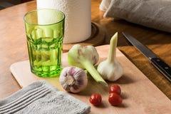 新鲜的年轻大蒜、刀子、小蕃茄和水一块绿色玻璃在厨房用桌上的 免版税图库摄影