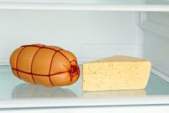 新鲜的开胃香肠和乳酪在冰箱架子 图库摄影