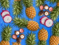新鲜的异乎寻常的果子,安排在蓝色背景 桃红色龙果子、黄色菠萝和紫色山竹果树 免版税库存照片