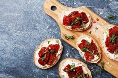 新鲜的意大利三明治用乳脂干酪和各式各样的蕃茄在木厨房上顶视图 可口快餐和开胃菜 免版税库存照片