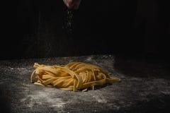 新鲜的意大利未煮过的自创面团 做面团的手 ?? 新鲜的意大利意粉 做的过程特写镜头  免版税库存图片