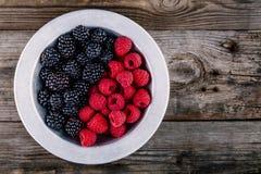 新鲜的成熟有机莓和黑莓在一个碗在木背景 免版税库存照片
