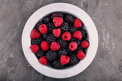 新鲜的成熟有机莓和黑莓在一个碗在灰色背景 免版税库存照片
