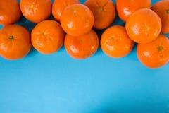 新鲜的成熟水多的果子普通话或蜜桔在蓝色台式视图被隔绝的橙皮 有一个开放领域为 免版税库存照片