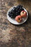 新鲜的成熟秋天果子苹果和葡萄在白色板材在土气木背景,顶视图 空位 库存照片