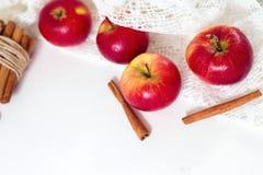 新鲜的成熟红色苹果和肉桂条在白色木背景 免版税库存照片