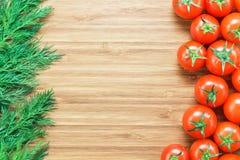 新鲜的成熟红色西红柿和新鲜的绿色莳萝在一个木切板 自然菜概念 健康d的背景 免版税库存照片