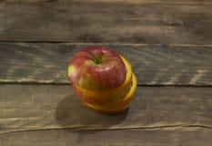 新鲜的成熟苹果和桔子在一张木桌上 免版税库存照片