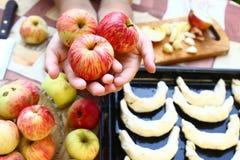新鲜的成熟苹果在手上用在背景的新月形面包 免版税库存图片