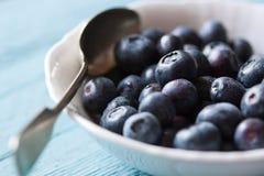 新鲜的成熟蓝莓特写镜头在一个碗的在蓝色木背景 免版税库存图片