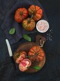 新鲜的成熟hairloom蕃茄和蓬蒿叶子在土气木板在黑石背景 库存图片