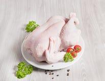 新鲜的整个未加工的鸡用荷兰芹和西红柿 免版税库存照片