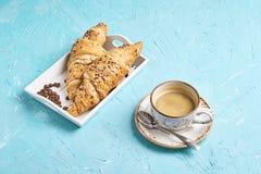 新鲜的整粒新月形面包和咖啡在蓝色桌上的 库存图片