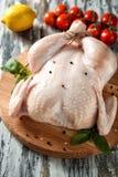 新鲜的整鸡用蕃茄和柠檬 图库摄影