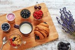新鲜的新月形面包、莓果、酸奶、玉米片和杯子在一张木桌上的牛奶 库存照片