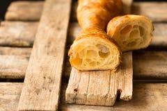 新鲜的新月形面包切成了两半用在可看见里面的酥饼,在葡萄酒木背景,关闭,亲属 免版税库存照片