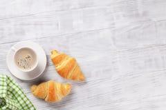 新鲜的新月形面包和咖啡 库存照片