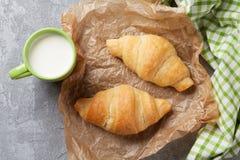 新鲜的新月形面包和牛奶 免版税库存图片