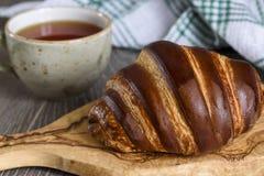 新鲜的新月形面包和茶杯早餐在木葡萄酒桌上 免版税库存照片