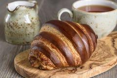 新鲜的新月形面包和茶杯早餐在木葡萄酒桌上 库存照片