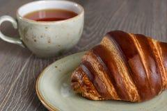 新鲜的新月形面包和茶杯早餐在木葡萄酒选项 库存照片