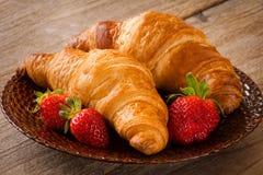 新鲜的新月形面包用在板材,早餐,温暖的口气的草莓 库存照片
