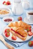 新鲜的新月形面包用果酱和草莓早餐 库存照片
