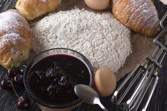 新鲜的新月形面包用面粉、樱桃果酱、把柄搅拌器和鸡蛋 免版税库存照片