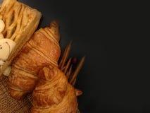 新鲜的新月形面包面包店面包在木表上的 免版税库存照片