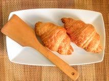 新鲜的新月形面包面包店面包在木表上的 库存图片