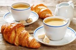 新鲜的早餐用新月形面包、浓咖啡和牛奶 免版税图库摄影