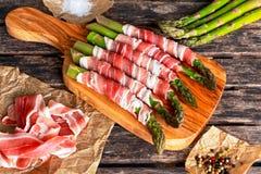 新鲜的有机未加工的烟肉包裹了在木桌上的芦笋 免版税库存照片
