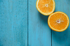 新鲜的有机桔子对分在蓝色木背景的果子 免版税图库摄影
