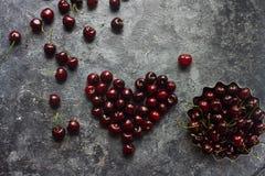新鲜的有机樱桃在黑暗的石背景的心脏形状结合了 图库摄影