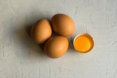 新鲜的有机红皮蛋,破裂的壳,白色具体桌表面,顶视图上的开放明亮的卵黄质,抽象 库存照片