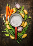 新鲜的有机菜和草本在老空的烹调罐附近在土气木背景,顶视图组成 免版税库存照片