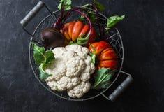 新鲜的有机菜-花椰菜,蕃茄,在葡萄酒的甜菜金属化在黑暗的背景的篮子 库存图片