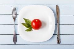新鲜的有机蕃茄和蕃茄叶子在白色板材 叉子和刀子在木桌上 健康概念的食物 顶视图 免版税图库摄影