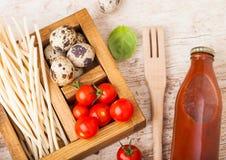 新鲜的有机hommemade意粉面团用鹌鹑蛋和新鲜的蕃茄与瓶西红柿酱和木小铲和basi 免版税库存图片