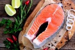 新鲜的未加工的三文鱼片断用在老木背景的有机荷兰芹 库存图片