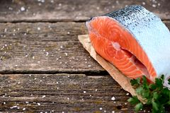 新鲜的未加工的三文鱼片断用在老木背景的有机荷兰芹 免版税库存照片