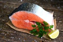 新鲜的未加工的三文鱼片断用在老木背景的有机荷兰芹 图库摄影