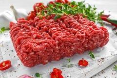 新鲜的未加工的与盐、胡椒、辣椒和新鲜的麝香草的牛肉肉末在白板 免版税图库摄影
