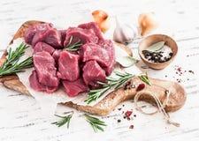 新鲜的未加工的切好的牛肉、香料和草本在一个橄榄色的委员会 免版税图库摄影