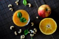 新鲜的未加工的橙色圆滑的人用苹果、红萝卜和坚果在黑暗的背景 图库摄影