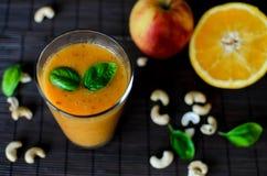 新鲜的未加工的橙色圆滑的人用苹果、红萝卜和坚果在黑暗的背景 免版税库存照片