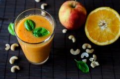 新鲜的未加工的橙色圆滑的人用苹果、红萝卜和坚果在黑暗的背景 免版税图库摄影