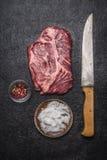 新鲜的未加工的牛排用红辣椒和盐与刻刀在一张黑暗的土气背景顶视图 免版税库存照片