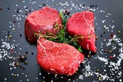 新鲜的未加工的牛肉小腓厉牛排,与盐、干胡椒和麝香草 库存照片