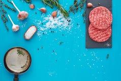 新鲜的未加工的牛肉肉用草本和盐在绿松石背景 图库摄影